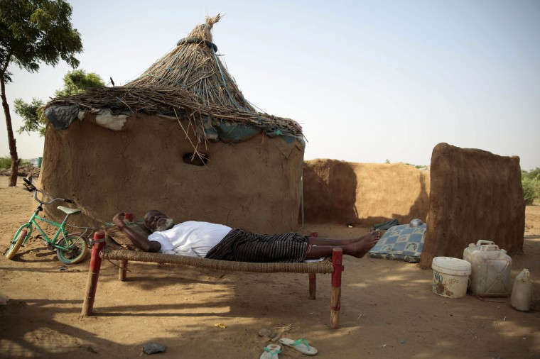 In this photo taken on Friday, Oct. 7, 2016, an elderly man lies on a bed in front of his hut at a camp for internally displaced people near the town of Abs, located on Yemen's western coastal plain below towering desert mountains. Hundreds of Yemenis fleeing war are now living in tents and mud-brick shelters scattered across a cornfield, where they buried the remains of loved ones they carried with them when they escaped. (AP Photos / Hani Mohammed)