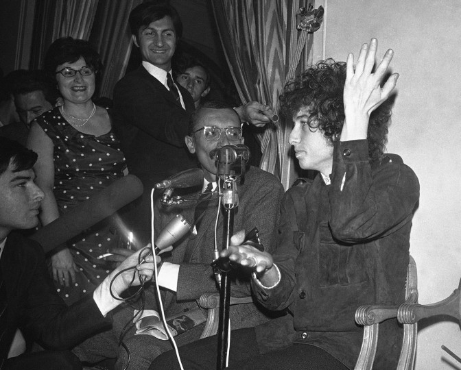 "FILE - In this May 22, 1966, file photo, Bob Dylan gestures during a news conference in Paris, France. Dylan won the 2016 Nobel Prize in literature on Thursday, Oct. 13, 2016, a stunning announcement that for the first time bestowed the prestigious award on a musician for ""having created new poetic expressions within the great American song tradition."" (AP Photo/Pierre Godot, File)"