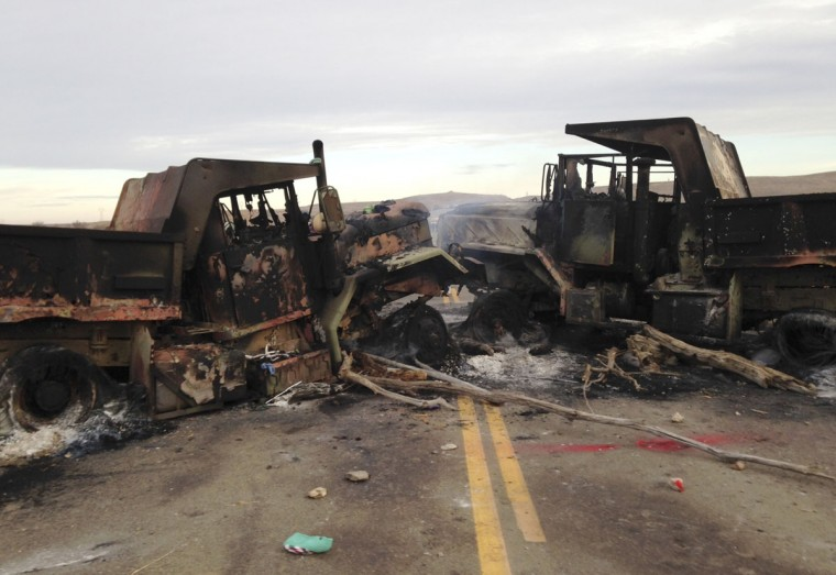 The burned hulks of heavy trucks sit on Highway 1806 near Cannon Ball, N.D., on Friday, Oct. 28, near the spot where protesters of the Dakota Access pipeline were evicted from private property a day earlier. Authorities say protesters burned several pieces of construction equipment Thursday during a chaotic confrontation with law enforcement. (AP Photo/James MacPherson)