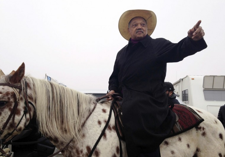 "Civil rights activist Jesse Jackson sits atop a horse Wednesday, Oct. 26, 2016, while visiting the protest camp against the Dakota Access oil pipeline outside Cannon Ball, N.D. Jackson said he came ""to pray together, protest together and if necessary, go to jail together."" (AP Photo/James MacPherson)"