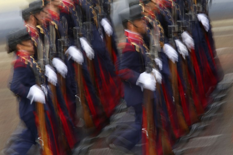 "In this photo taken with a slow shutter speed, Spanish soldiers march in a military parade during a national holiday known as ""Dia de la Hispanidad"" or Hispanic Day, in Madrid, Spain, Wednesday, Oct. 12, 2016. Almost a year into Spain's political deadlock, the country is celebrating its National Day with a military parade of over 3,000 soldiers marching through Madrid and aircraft drawing trails of red and yellow smoke in the sky to represent the flag. (AP Photo/Francisco Seco)"