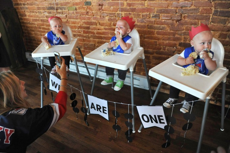 From left, Kristen Hewitt takes cell phone pictures of Trip, Finn and Ollie as they demolish their birthday cake at a party held at Cafe Hon. The identical triplets turned one on Oct. 6. (Amy Davis/ Baltimore Sun)