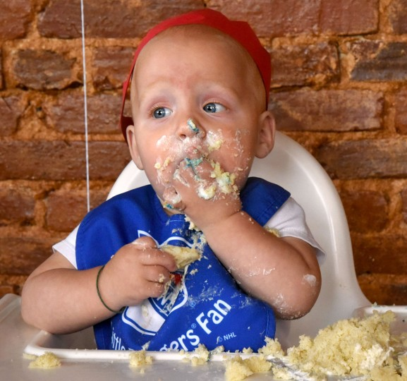 Finn is covered in crumbs and cake frosting as he demolishes his portion of the birthday cake. The birthday celebration for family and friends of the Hewitt triplets was held at Cafe Hon. The identical triplets turned one on Oct. 6. (Amy Davis/ Baltimore Sun)
