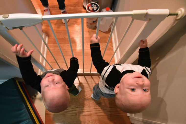 Finn, left, and Trip, right, look like they are ready for a breakout from jail. The triplets can stand with one hand holding onto a support for balance, and are eager to get around the safety gates in their house. (Amy Davis/ Baltimore Sun)