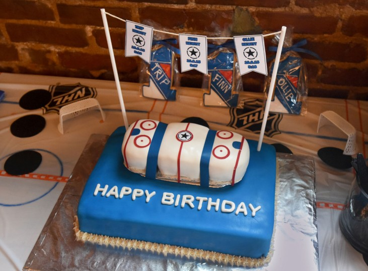 A friend made the hockey-themed birthday cake for the Hewitt triplets. The top piece, decorated like a hockey rink, was divided into three portions for the boys, who turned one on Oct. 6. The flags above the cake give their birth order. (Amy Davis/ Baltimore Sun)