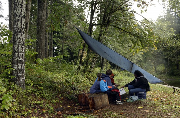 In this Oct. 6, 2016 photo, Outdoors School students gather for a lesson under a canopy in the forest at Camp Howard in Mount Hood National Forest near Corbett, Ore. The outdoor education is unique to Oregon and is a rite-of-passage for public school students that's meant to instill a respect for nature in each generation - studies show it improves attendance and boosts test scores. (AP Photo/Don Ryan)