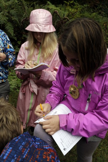 In this Oct. 6, 2016 photo, Outdoor School students Maya Herring, left, and Evie Larson enter notes in their field study notebooks during a lesson at Camp Howard in Mount Hood National Forest near Corbett, Ore. The outdoor education is unique to Oregon and is a rite-of-passage for public school students that's meant to instill a respect for nature in each generation - studies show it improves attendance and boosts test scores. (AP Photo/Don Ryan)