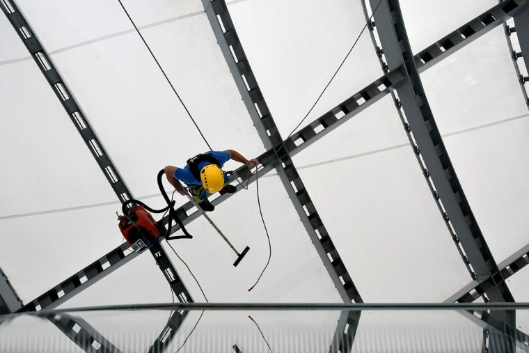 "A man works on the structure of the new convention center named ""The cloud"" (""La Nuvola"" in Italian) designed by Italian architect Massimiliano Fuksas on October 19, 2016 in the Eur business district in Rome. The congress center will be inaugurated on October 29, 2016. (ALBERTO PIZZOLI/AFP/Getty Images)"