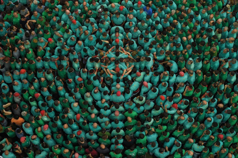 """Members of the """"Colla Jove Xiquets de Tarragona"""" human tower team form a """"castell"""" (human tower) during the XXVI human towers, or 'castells', competetion in Tarragona on October 2, 2016. These human towers, built traditionally in festivals within Catalonia, gather several teams that attempt to build and dismantle a human tower structure. (LLUIS GENE/AFP/Getty Images)"""