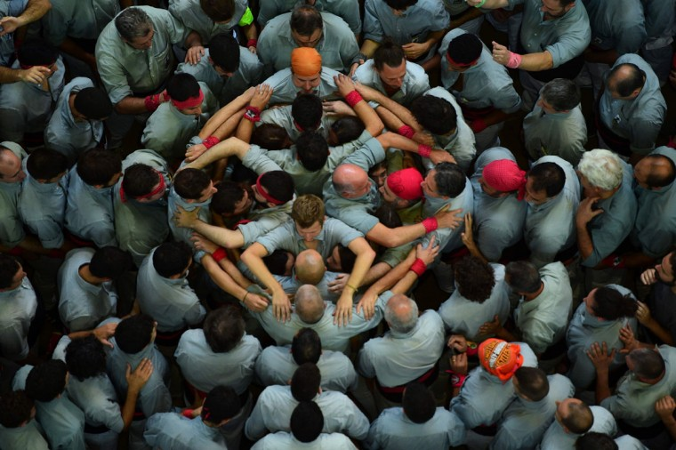 """Members of the """"Colla Vella dels Xiquets de Valls"""" human tower team form a """"castell"""" (human tower) during the XXVI human towers, or 'castells', competetion in Tarragona on October 2, 2016. These human towers, built traditionally in festivals within Catalonia, gather several teams that attempt to build and dismantle a human tower structure. (LLUIS GENE/AFP/Getty Images)"""