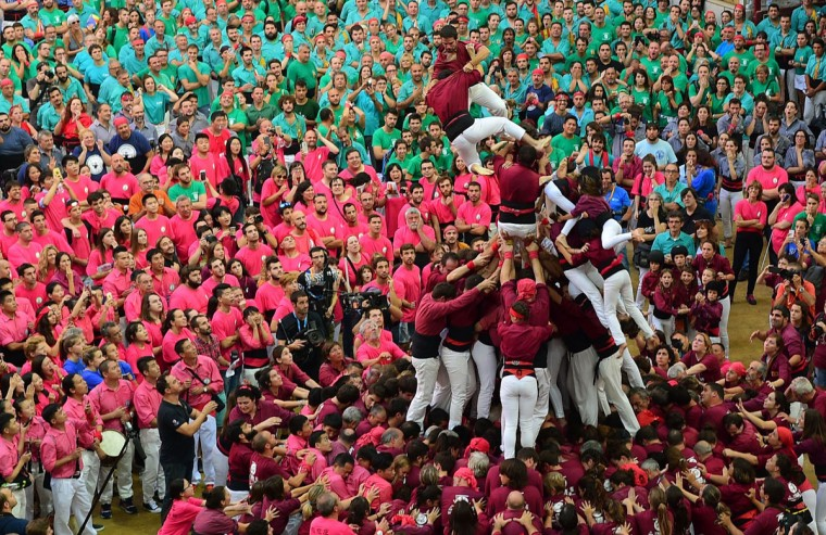 """Members of the """"Xics de Granollers"""" human tower team fall as they attempt to form a """"castell"""" during the XXVI human towers, or castells, competetion in Tarragona on October 1, 2016. These human towers, built traditionally in festivals within Catalonia, gather several teams that attempt to build and dismantle a tower structure. (LLUIS GENE/AFP/Getty Images)"""