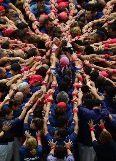 """Members of the """"Colla Xiquets del Serrallo"""" human tower team form a """"castell"""" during the XXVI human towers, or castells, competetion in Tarragona on October 1, 2016. These human towers, built traditionally in festivals within Catalonia, gather several teams that attempt to build and dismantle a tower structure. (LLUIS GENE/AFP/Getty Images)"""