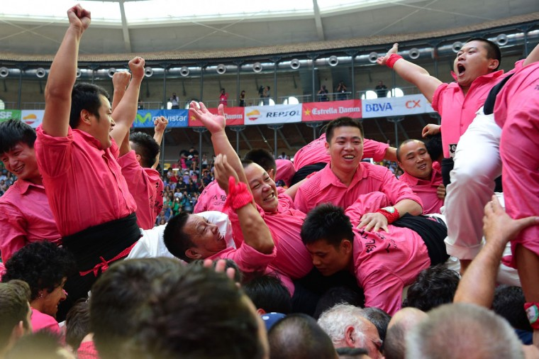"""Members of the Chinese """"Xiquets de Hangzhou"""" human tower team celebrate after forming a """"castell"""" during the XXVI human towers, or castells, competetion in Tarragona on October 1, 2016. These human towers, built traditionally in festivals within Catalonia, gather several teams that attempt to build and dismantle a tower structure. (LLUIS GENE/AFP/Getty Images)"""