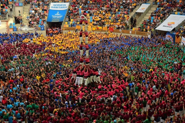 """Members of the Chinese """"Xiquets de Hangzhou"""" human tower team form a """"castell"""" during the XXVI human towers, or castells, competetion in Tarragona on October 1, 2016. These human towers, built traditionally in festivals within Catalonia, gather several teams that attempt to build and dismantle a tower structure. (LLUIS GENE/AFP/Getty Images)"""