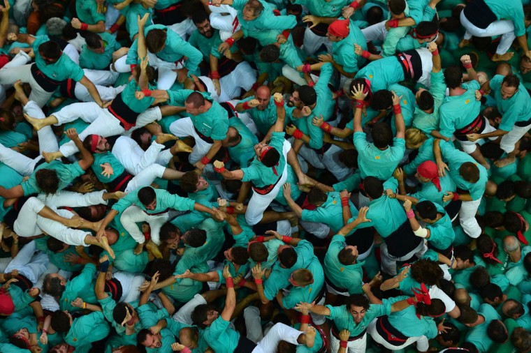 """Members of the """"Colla Jove Xiquets de Tarragona"""" human tower team celebrate after forming their """"castell"""" (human tower) during the XXVI human towers, or 'castells', competetion in Tarragona on October 2, 2016. These human towers, built traditionally in festivals within Catalonia, gather several teams that attempt to build and dismantle a human tower structure. (LLUIS GENE/AFP/Getty Images)"""