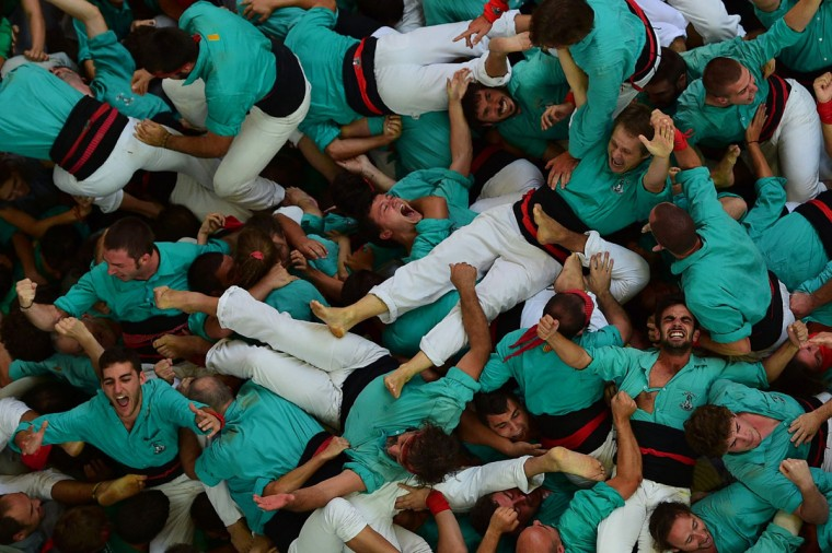 """Members of the """"Castellers de Vilafranca"""" human tower team celebrate after forming their """"castell"""" (human tower) during the XXVI human towers, or 'castells', competetion in Tarragona on October 2, 2016. These human towers, built traditionally in festivals within Catalonia, gather several teams that attempt to build and dismantle a human tower structure. (LLUIS GENE/AFP/Getty Images)"""