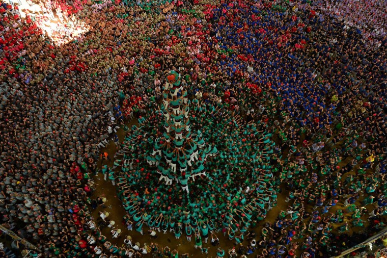 """Members of the """"Castellers de Vilafranca"""" human tower team form a """"castell"""" (human tower) during the XXVI human towers, or 'castells', competetion in Tarragona on October 2, 2016. These human towers, built traditionally in festivals within Catalonia, gather several teams that attempt to build and dismantle a human tower structure. (LLUIS GENE/AFP/Getty Images)"""