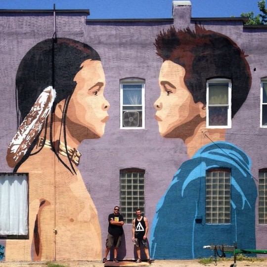 """Gregg Deal, who belongs to Nevada's Pyramid Lake Paiute tribe, doesn't overtly claim land as Indian in his work, rather he reflects the subtleties of what it means to be an American Indian in a nation where Indian presence has been all but erased. The above portrait, """"The Duality Of Indigeneity,"""" in Baltimore shows two boys facing each other -- one with long hair, the other in a hoodie. """"Which one's more Indian?"""" Deal said. """"And the answer is that they're both Indian."""" (Photo courtesy of the artist)"""