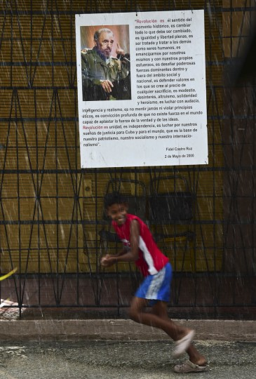 A child runs in front of a poster of Cuban revolutionary leader Fidel Castro, in Havana, on November 27, 2016, two days after his death. Cuban revolutionary icon Fidel Castro died late November 25 in Havana, his brother, President Raul Castro, announced on national television. Castro's ashes will be buried in the historic southeastern city of Santiago on December 4 after a four-day procession through the country. (AFP PHOTO/RONALDO SCHEMIDT)
