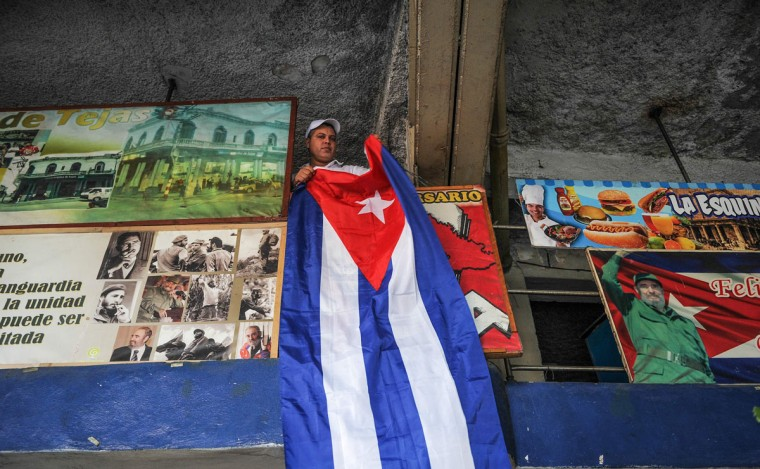 A man places a Cuban national flag in his restaurant in Havana, on November 27, 2016, two days after Cuban leader Fidel Castro died. Cuban revolutionary icon Fidel Castro died late November 25 in Havana, his brother, President Raul Castro, announced on national television. Castro's ashes will be buried in the historic southeastern city of Santiago on December 4 after a four-day procession through the country. (AFP PHOTO/YAMIL LAGE)