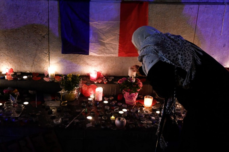 A woman lights a candle next to a French national flag at a makeshit memorial at the Marianne statue of the place de la Republique in Paris on November 13, 2016 as France marked the first anniversary of the Paris attacks. 130 people were killed on November 13, 2015 by gunmen and suicide bombers from the Islamic State (IS) group in a series of coordinated attacks in and around Paris. (AFP PHOTO / ALAIN JOCARD)