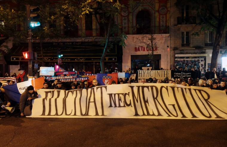 """French Paris Saint Germain football club's supporters display a banner created by the city of Paris, reading """"Fluctuat Nec Mergitur"""" (tossed but not sunk) in front of the Bataclan concert hall in Paris on November 13, 2016 as France marked the first anniversary of the Paris attacks with sombre ceremonies and painful memories for the relatives of the 130 people killed. 130 people were killed on November 13, 2015 by gunmen and suicide bombers from the Islamic State (IS) group in a series of coordinated attacks in and around Paris. (AFP PHOTO / JOEL SAGET)"""