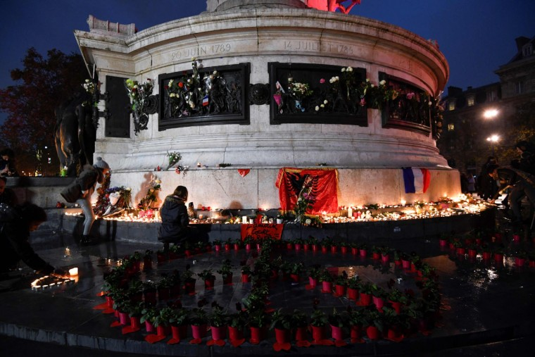People light candles at a makeshit memorial at the bottom of the Marianne statue on place de la Republique in Paris on November 13, 2016 as France marked the first anniversary of the Paris attacks with sombre ceremonies and painful memories for the relatives of the 130 people killed. 130 people were killed on November 13, 2015 by gunmen and suicide bombers from the Islamic State (IS) group in a series of coordinated attacks in and around Paris. (AFP PHOTO / ALAIN JOCARD)