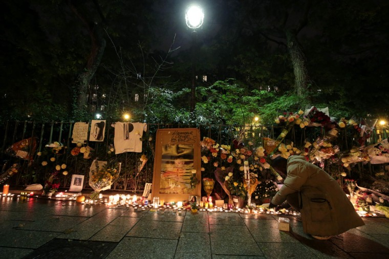 A man lights a candle at a makeshift memorial near the Bataclan concert hall in Paris on November 13, 2016 as France marked the first anniversary of the Paris attacks with sombre ceremonies and painful memories for the relatives of the 130 people killed. 130 people were killed on November 13, 2015 by gunmen and suicide bombers from the Islamic State (IS) group in a series of coordinated attacks in and around Paris. (AFP PHOTO / JOEL SAGET)