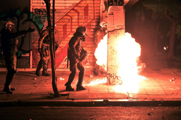 Fire from a molotov cocktail rises near Greek riot police during clashes around the Polytechnic school, following a protest against the visit of the US president in Athens on November 15, 2016. US President Barack Obama is in Greece on a two-day official visit. (Louisa Gouliamaki/AFP/Getty Images)