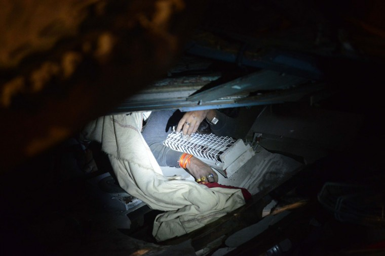 A dead body is lightened in the wreckage of a derailed train near Pukhrayan in Kanpur district on November 20, 2016. Emergency workers raced to find any more survivors in the mangled wreckage of an Indian train that derailed on Novcember 20, killing at least 120 people, in the worst disaster to hit the country's ageing rail network in recent years. Shocked passengers recalled being jolted out of their early morning slumber by a violent thud as 14 carriages leapt from the tracks in a remote area near Kanpur city in Uttar Pradesh state. (AFP PHOTO / SANJAY KANOJIA)