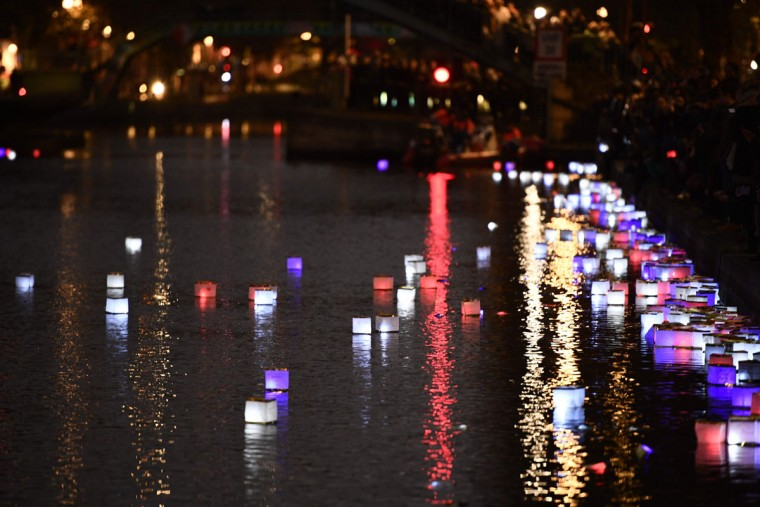 """People set afloat lanterns during a lantern ceremony given by the association """"ToujoursParis.fr"""" at the Canal Saint-Martin in Paris on November 13, 2016 to mark the first anniversary of the Paris terror attacks. 130 people were killed on November 13, 2015 by gunmen and suicide bombers from the Islamic State (IS) group in a series of coordinated attacks in and around Paris. (AFP PHOTO / Martin BUREAU)"""