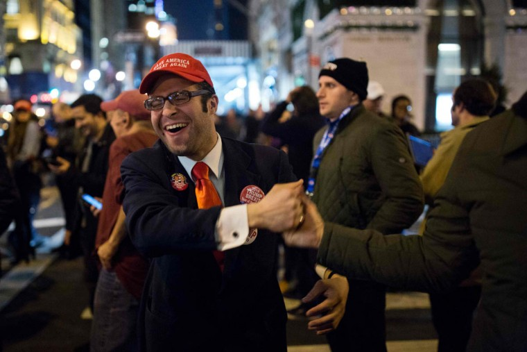 A supporter of Republican presidential nominee Donald Trump reacts to updates from the election returns outside Trump Tower in New York City after midnight on election day November 9, 2016. Donald Trump stunned America and the world, riding a wave of populist resentment to defeat Hillary Clinton in the race to become the 45th president of the United States. The Republican mogul defeated his Democratic rival, plunging global markets into turmoil and casting the long-standing global political order, which hinges on Washington's leadership, into doubt. / AFP PHOTO / Dominick Reuter