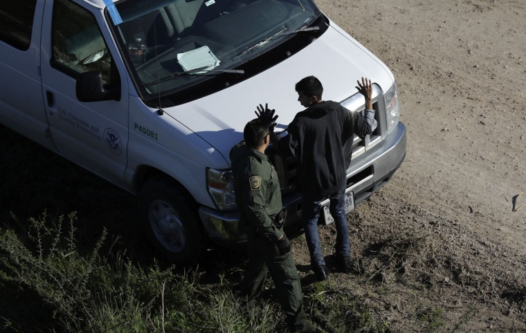 In this Wednesday, Nov. 16, 2016, photo, a U.S. Customs and Border Patrol agent works with a suspected immigrant entering the country illegally along the Rio Grande in Hidalgo, Texas. (AP Photo/Eric Gay)