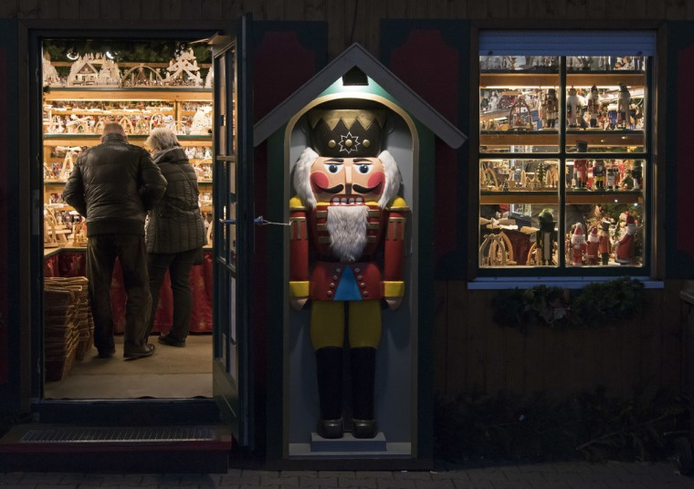 People visit a stand decorated with a nutcracker during the Christmas Fair in Erfurt, central Germany, Monday, Nov. 28, 2016. The Erfurt Christmas Market is one of the most beautiful Christmas Markets in the whole of Germany. The square is beautifully decorated with a huge, candle-lit Christmas tree and a large, hand-carved wooden creche. (AP Photo/Jens Meyer)