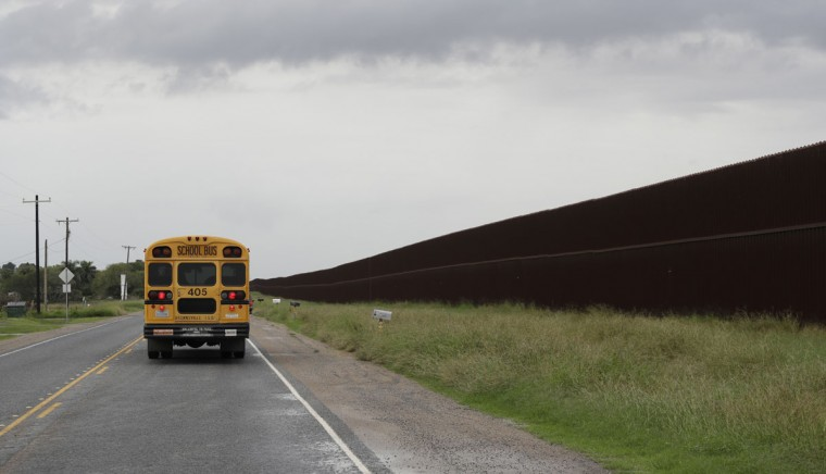 In this Monday, Nov. 14, 2016, photo, a school bus passes a section of border fence in Brownsville, Texas. The idea of a concrete wall spanning the entire 1,954-mile southwest frontier collides head-on with multiple realities, like a looping Rio Grande, fierce local resistance, and cost. (AP Photo/Eric Gay)