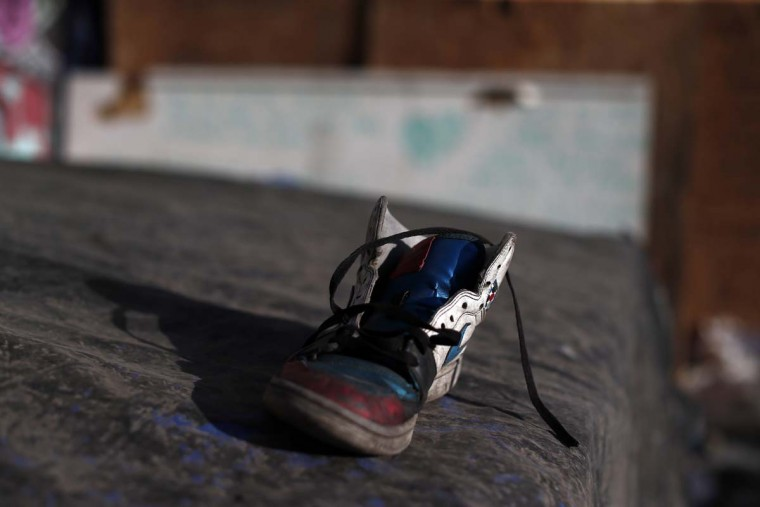 In this Oct. 10, 2016 photo, a discarded shoe lays on top a tarp used by street children for shelter in a ruined building in Santiago, Chile. Many if not all of the youths living in the ruin were once wards of the state, living in shelters of National Service for Minors. (AP Photo/Luis Hidalgo)