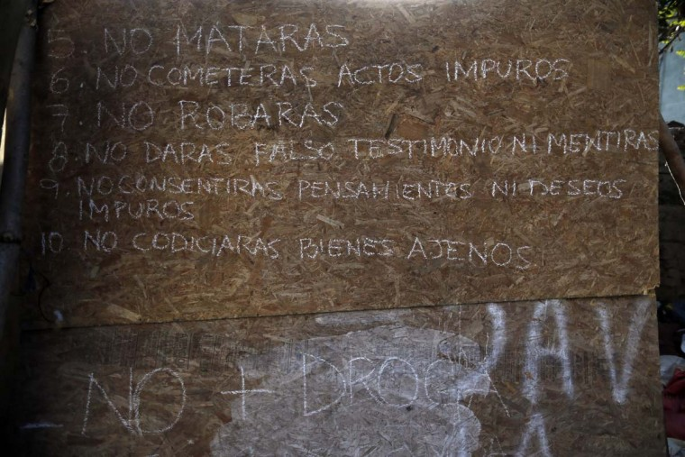 "In this Oct. 10, 2016 photo, the ten commandments are displayed on a piece of plywood, with the extra ""No More Drugs,"" added at the bottom, in a ruined abandoned building used by street children for shelter, in Santiago, Chile. Many if not all of the youths living in the ruin were once wards of the state, living in shelters of National Service for Minors. (AP Photo/Luis Hidalgo)"