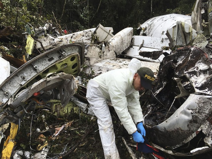A police officer works at the wreckage site of a chartered airplane that crashed in La Union, a mountainous area outside Medellin, Colombia, Tuesday, Nov. 29, 2016. The plane was carrying the Brazilian first division soccer club Chapecoense team that was on it's way for a Copa Sudamericana final match against Colombia's Atletico Nacional. (Photo/Colombia National Police via AP)