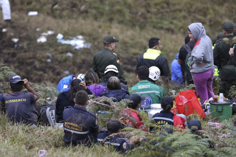 Rescue workers take a break at the wreckage site of an airplane crash, in La Union, a mountainous area near Medellin, Colombia, Tuesday , Nov. 29, 2016. The chartered plane was carrying a Brazilian soccer team to the biggest match of its history when it crashed into a Colombian hillside and broke into pieces, killing 75 people and leaving six survivors, Colombian officials said Tuesday. (AP Photo/Fernando Vergara)