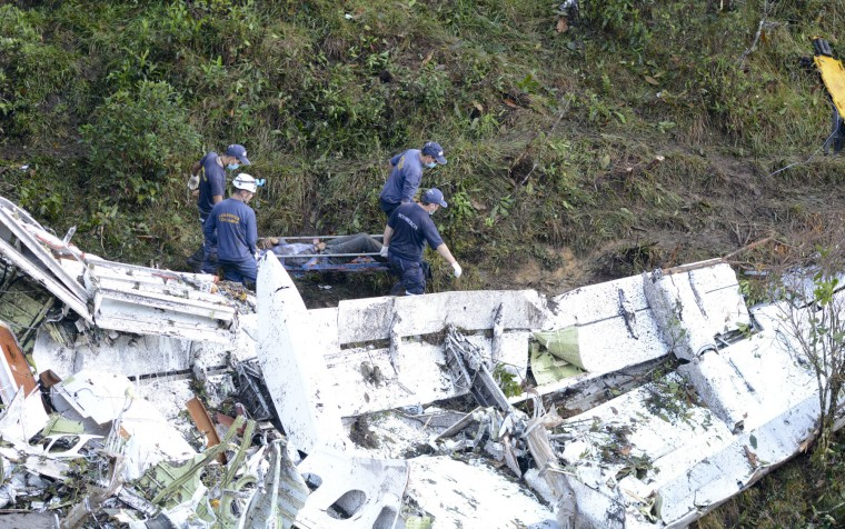Rescue workers recover a body from the wreckage site of an airplane crash, in La Union, a mountainous area near Medellin, Colombia, Tuesday , Nov. 29, 2016. The chartered plane was carrying a Brazilian soccer team to the biggest match of its history when it crashed into a Colombian hillside and broke into pieces, killing 75 people and leaving six survivors, Colombian officials said Tuesday. (AP Photo/Luis Benavides)