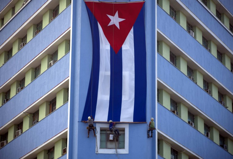 Workers hang a giant Cuban flag on a government building in Havana, Cuba, Sunday, Nov. 27, 2016, two days after the death of Fidel Castro. Cuba is observing nine days of mourning for the former president who ruled Cuba for half a century. (AP Photo/Ramon Espinosa)