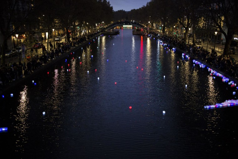People place colorful floating lanterns in the Canal Saint-Martin in Paris, France, Sunday, Nov. 13, 2016 during a ceremony held for the victims of last year's Paris attacks. ÔªøÔªøFrance marked the anniversary of Islamic extremists' coordinated attacks on Paris with a somber silence on Sunday that was broken only by voices reciting the names of the 130 slain, and the son of the first person to die stressing the importance of integration. (AP Photo/Kamil Zihnioglu)