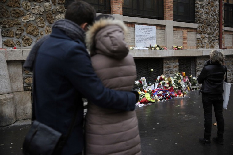 People pay respect in memory of the victims of the Nov. 13, in front of a commemorative plaque outside La Belle Equipe restaurant, in Paris, Sunday, Nov. 13, 2016. A year ago the Islamic State group brought its extremist war to Paris, seeding terror with attacks on a rock concert, the national stadium and bustling sidewalk cafes. (AP Photo/Christophe Ena)