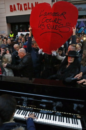 """A woman plays piano, next to a red heart reading """"Loves is in the streets"""" in front of the Bataclan concert hall in Paris, France, Sunday, Nov. 13, 2016 after a ceremony held for the victims of last year's Paris attacks which targeted the Bataclan concert hall as well as a series of bars and killed 130 people. (AP Photo/Francois Mori)"""