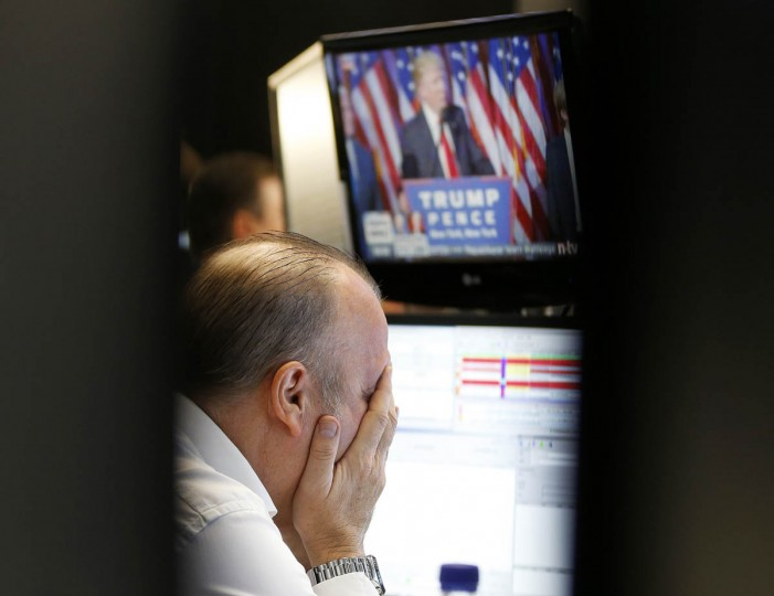 A broker reacts as newly elected US President Donald Trump shows up on a television screen at the stock market in Frankfurt, Germany, Wednesday, Nov. 9, 2016.(AP Photo/Michael Probst)