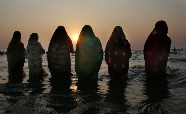 Hindu women offer prayers as the sun sets over the Arabian Sea during Chhath Puja festival in Mumbai, India, Sunday, Nov. 6, 2016. During this ancient Hindu festival, rituals are performed to thank the Sun God for sustaining life on earth. (AP Photo/Rafiq Maqbool)