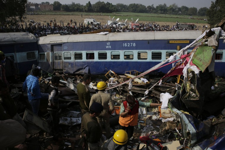 Rescuers stand amid debris after 14 coaches of an overnight passenger train rolled off the track near Pukhrayan village Kanpur Dehat district, Uttar Pradesh state, India, Sunday, Nov. 20, 2016. Dozens were killed and dozens more were injured in the accident. (AP Photo/Rajesh Kumar Singh)