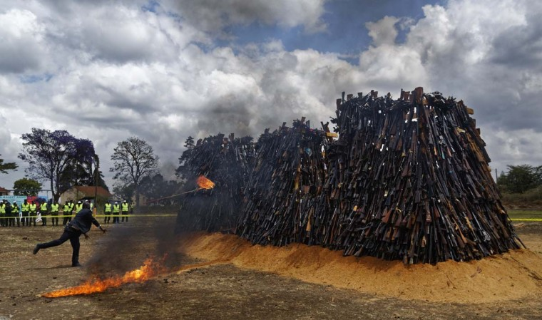 A man throws a torch to set light to a pile of 5,250 illegal weapons as they are burned by Kenyan police in Ngong, near Nairobi, in Kenya Tuesday, Nov. 15, 2016. The weapons consisted of both confiscated and surrendered firearms that had been stockpiled over almost a decade and were destroyed by police as a message to the public to surrender others. (AP Photo/Ben Curtis)