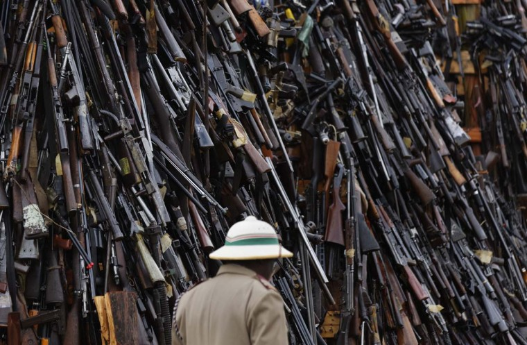 An official walks past a pile of 5,250 illegal weapons before they were burned by Kenyan police in Ngong, near Nairobi, in Kenya Tuesday, Nov. 15, 2016. The weapons consisted of both confiscated and surrendered firearms that had been stockpiled over almost a decade and were destroyed by police as a message to the public to surrender others. (AP Photo/Ben Curtis)