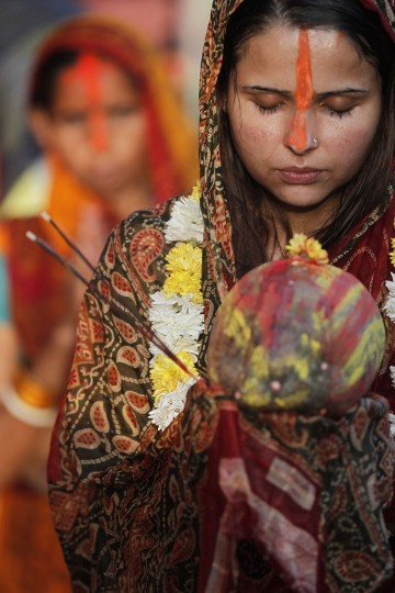 A Nepalese woman offers prayers to the setting Sun on the banks of the Bagmati River during the Chhath Puja festival in Kathmandu, Nepal, Sunday, Nov. 6, 2016. During Chhath, an ancient Hindu festival, rituals are performed to thank the Sun God for sustaining life on earth. (AP Photo/Niranjan Shrestha)